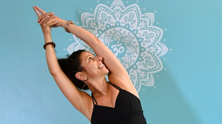 HAC Yoga Director Maria DiCamillo posing in front of blue wall with mandala