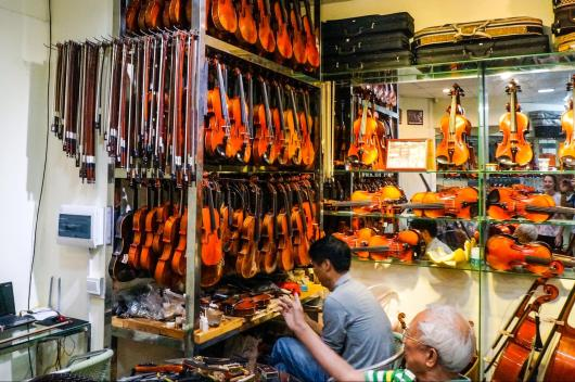 Violin shopkeeper modifying a violin according to his customer's request