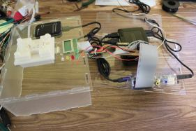 Disassembled, the programmer contains a Raspberry Pi, USB hub, CC-Debugger, USB thumb drive, custom electronics, and the pogo pin 3D printed holder.