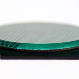 The side view of this tile shows the translucent blue-green disk, with the engraved pattern on the bottom.