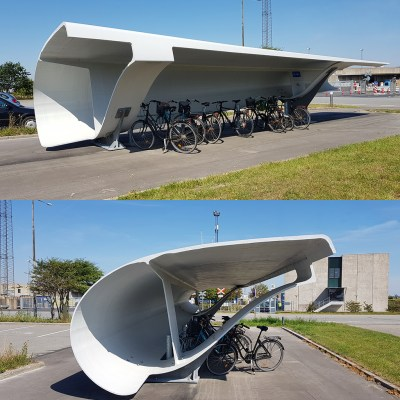 A picture of a wind turbine blade that has been turned into a bike shed.