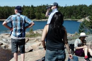 Kursledare och deltagare tittar ut över en sjö från en bergshäll.