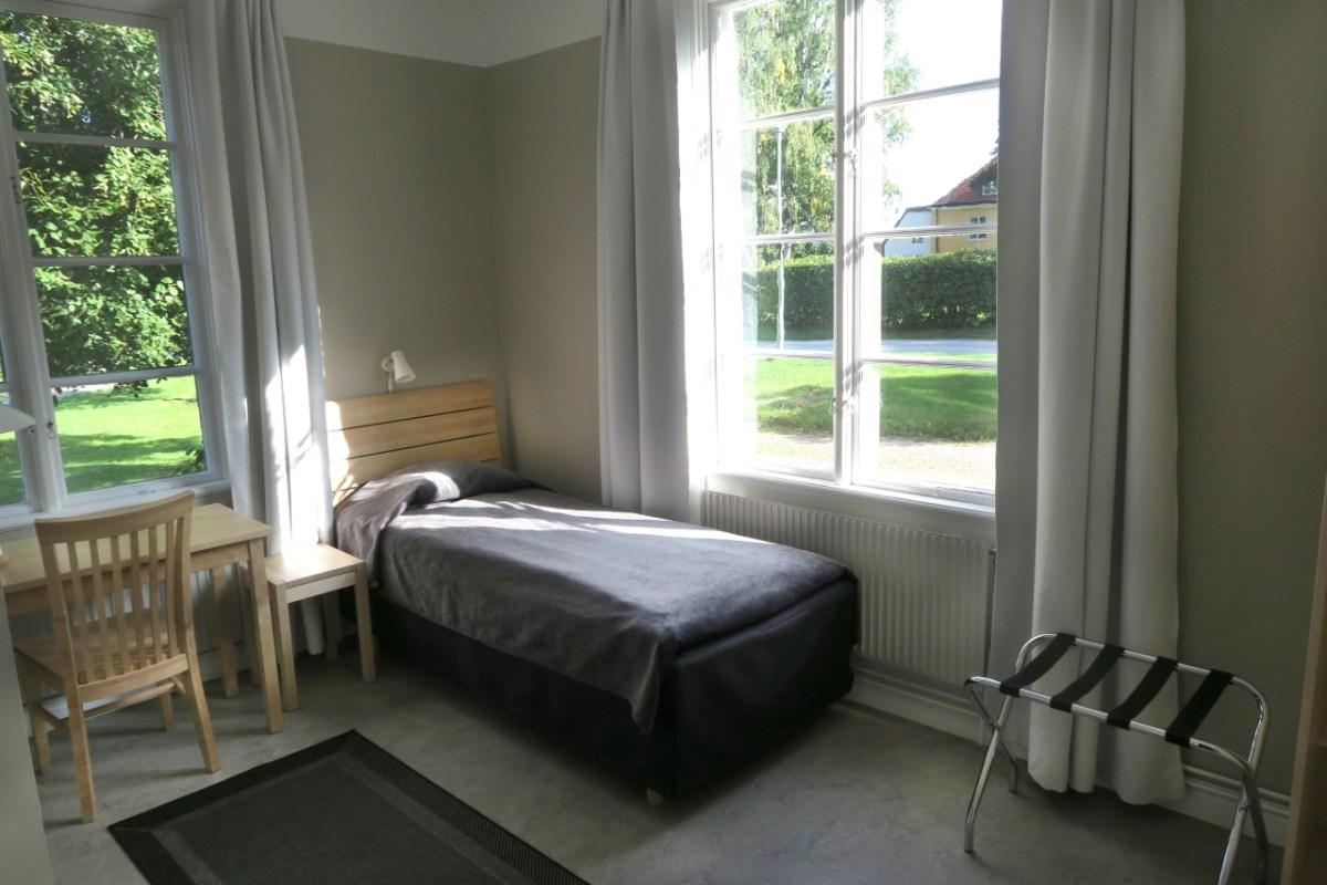 Rum på Nyvillan. Säng vid fönster.