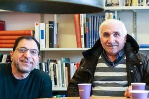 Två män ler med kaffekoppar framför sig.