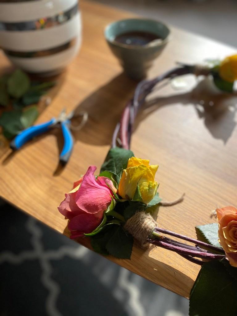 Binde blomsterkrans med roser, jutegarn og kvistkrans.