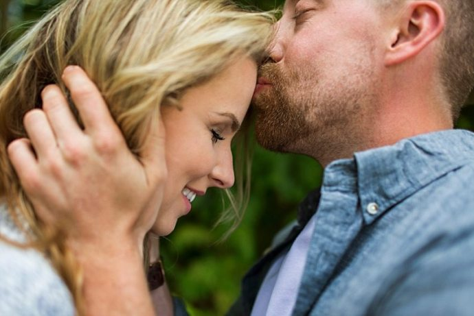 An engagement photo of a man kissing a woman's forehead.