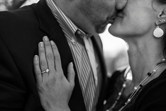 A black and white close-up of an engagement ring as the bride and groom kiss in the background.