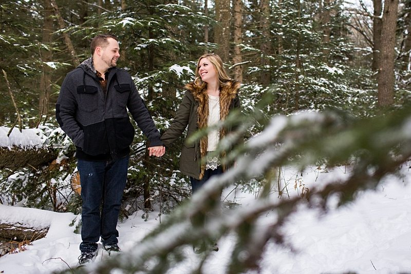 A couple holds hands in the snowy woods of Freeport, Maine.