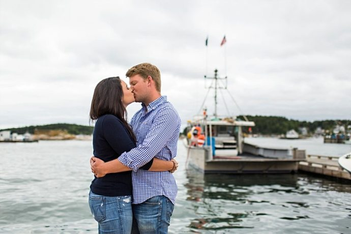 A couple kisses with boats in the background in Stonington, Maine.