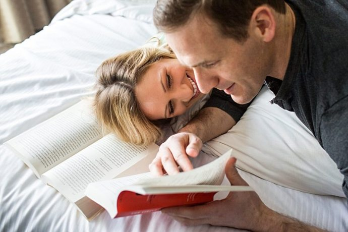 A couple reads together in bed.