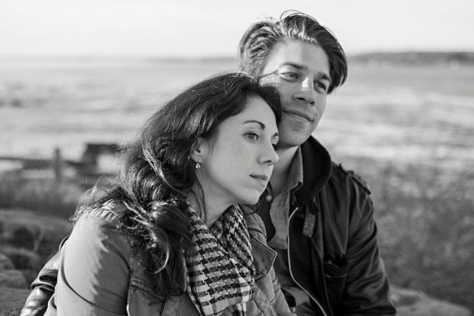 A black and white portrait of a couple sitting by the ocean.