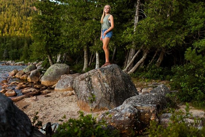 A senior poses on top of a giant rock at Jordan Pond.