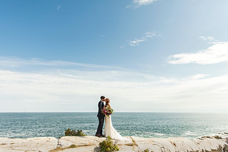 A portrait of a bride and groom kissing on the cliffs at Pemaquid Point Light on a sunny day.