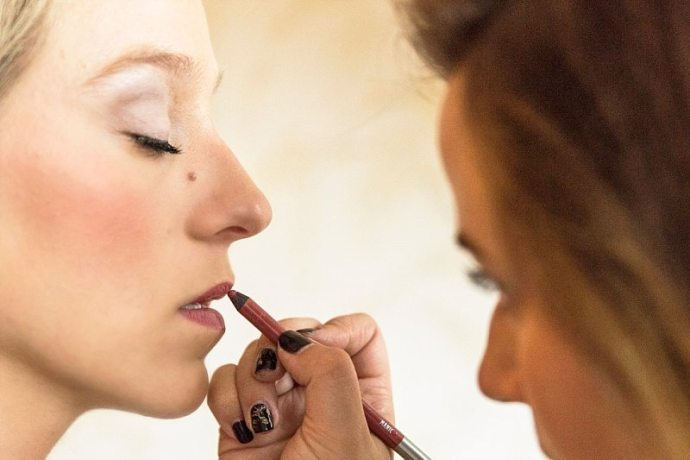 A close up of a makeup artist applying lip liner to the bride's lips.