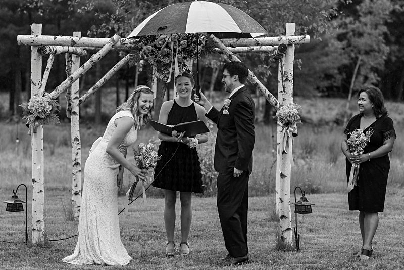 A bride and groom laugh as it rains during their ceremony. The groom holds an umbrella over them.