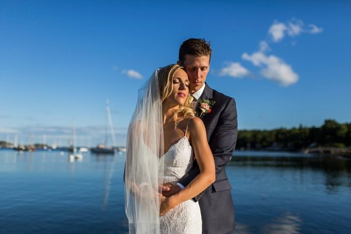 A bride and groom let the sun warm their faces at Rockport Harbor in Maine.
