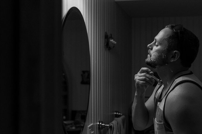 A dramatic black and white photo of a groom shaving his beard while looking into a mirror.