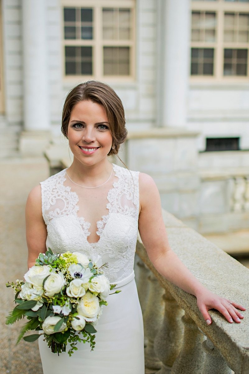 A posed portrait of a bride smiling outside Portland Maine City Hall with her bouquet.