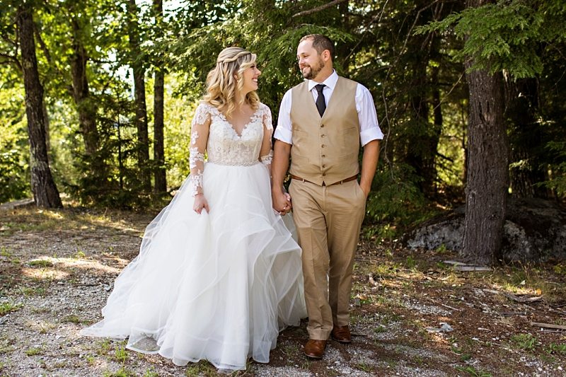 A bride and groom hold hands and smile at each other in Norway, Maine.