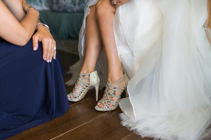 A close up of a bride's shoes that her sister has just places on her feet.