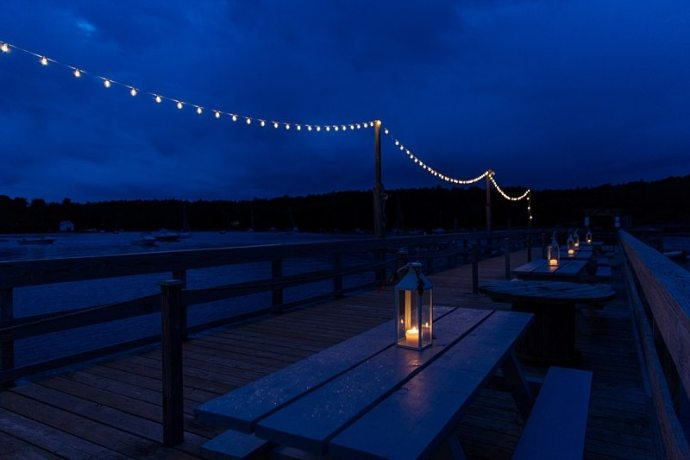 Twilight creates dark blue skies in this photo of lanterns and bistro lights lighting the outside of The Contented Sole in Maine.