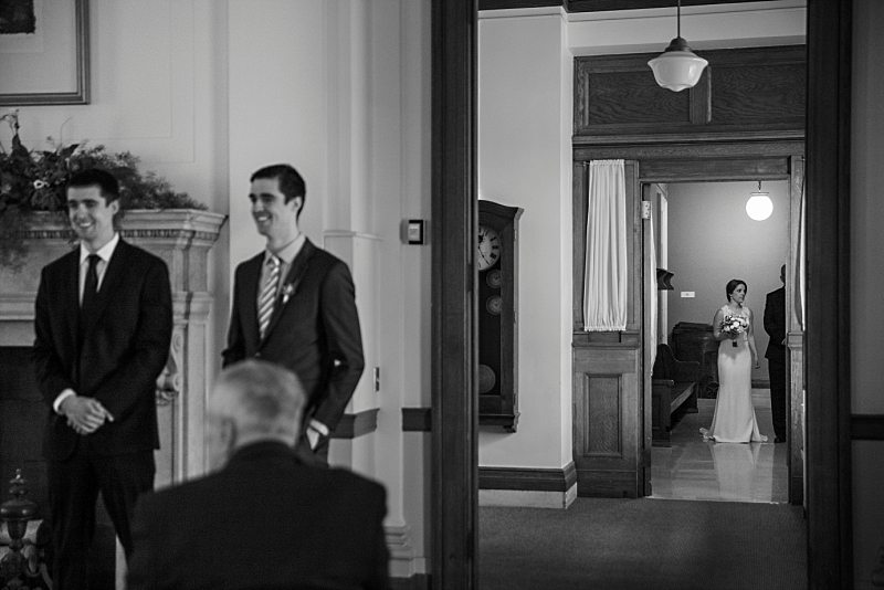 A black and white image of the bride waiting to enter the ceremony down the hall. The groom can be seen waiting and is slightly out of focus.