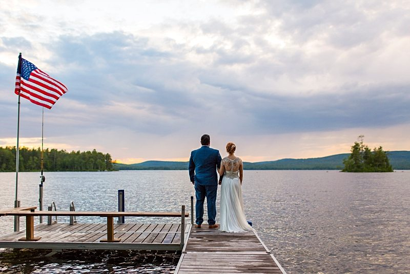 A bride and groom's backs as they face sunset on a dock with an American flag waving in the wind nearby.