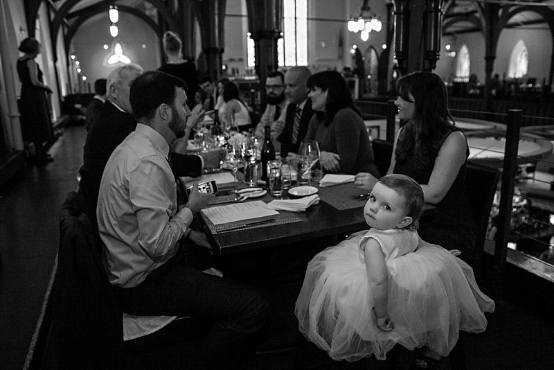 A flower girl looks unimpressed with the camera during the reception dinner.
