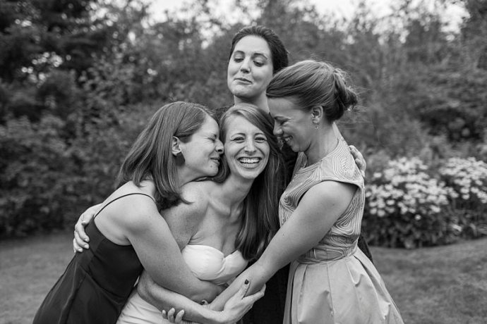 Bridesmaids tightly hug the bride and she laughs.