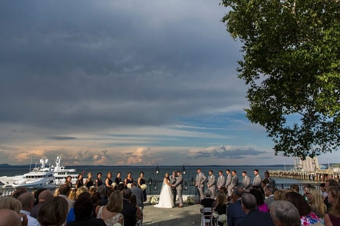 An intense spotlight on sun shines on a couple during their wedding ceremony with ominous storm clouds rolling in behind them.