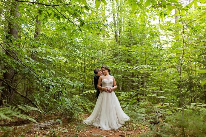 A portrait of a bride and groom standing in the Maine wilderness with their arms around each other.