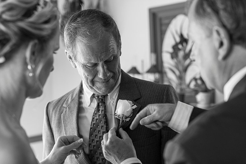 The bride and the groom's father try to pin a boutonniere on the bride's father.