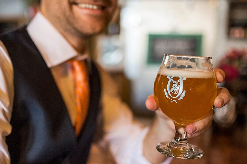 You can see a groom smiling in the background of this close-up of the beer he is holding.