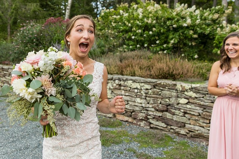 A bride screams in excitement when she sees someone at her wedding.