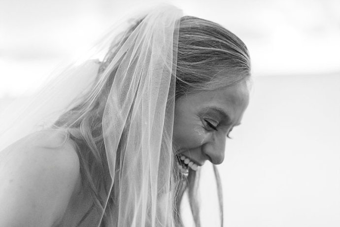 A black and white of a bride laughing with tear-stained cheeks during her wedding ceremony.