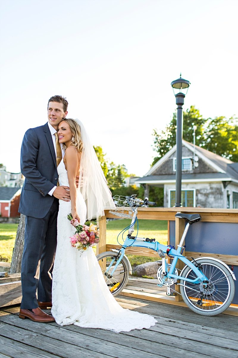 A bride and groom stand on a dock, looking out at the ocean, with a blue bicycle standing nearby.