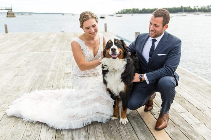 A bride and groom kneel with their dog for a portrait on the dock in Northeast Harbor, Maine.