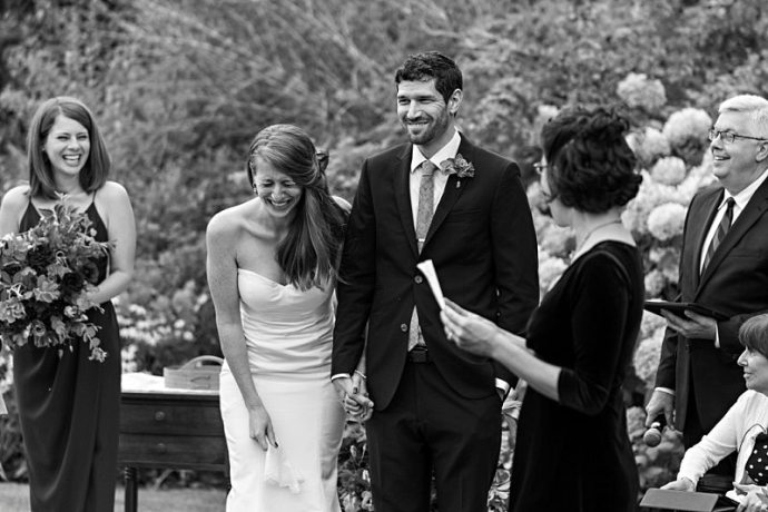 A bride and groom laugh during one of the readings during their wedding ceremony.
