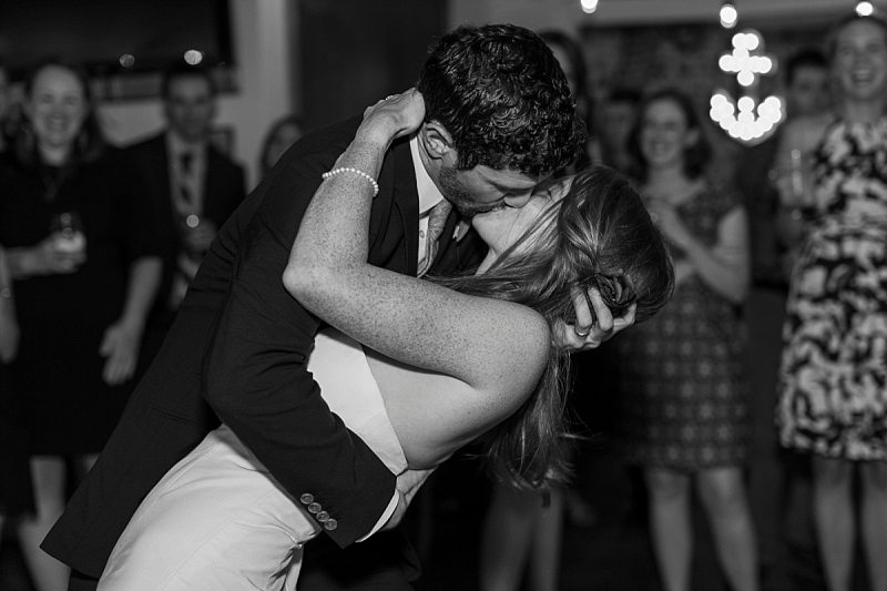 A groom dips his bride and kisses her at the end of their first dance.