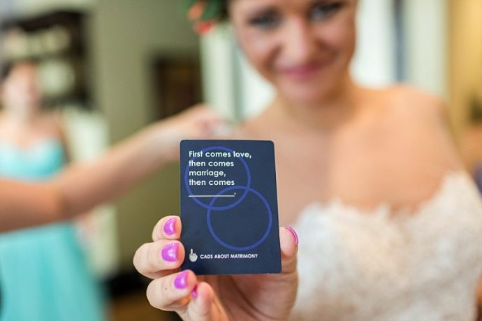 "A bride holds a card out at the camera that says, ""first comes love, then comes marriage, then comes (blank)."""