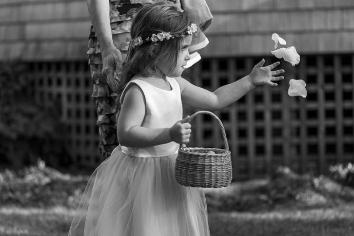 A flower girl focuses hard as she throws rose petals into the air.