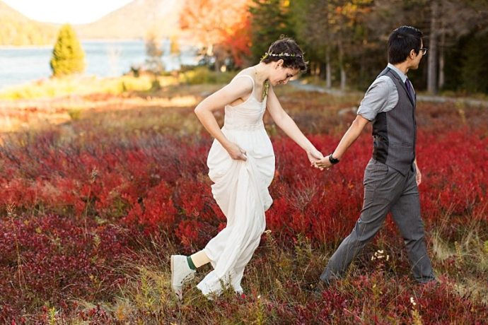 A bride and groom walk through colorful plants at Jordan Pond in Acadia National Park.