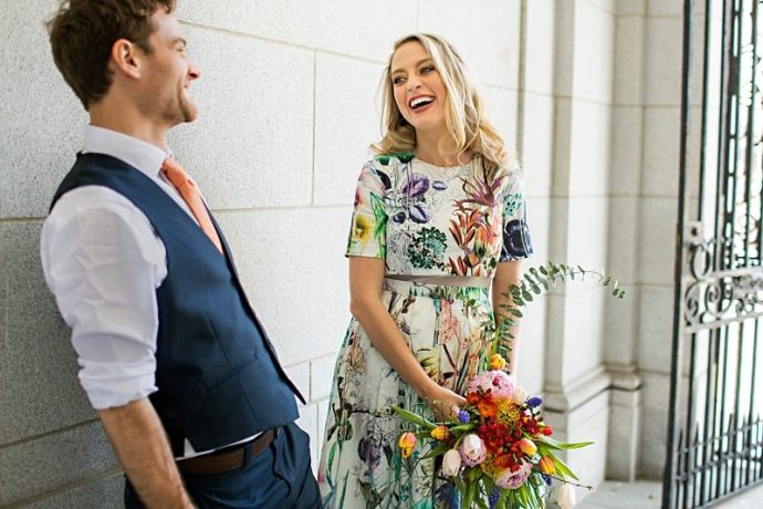 A portrait of a bride and groom laughing at each other.