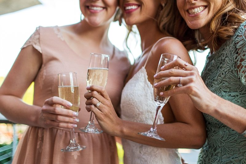 The bride and her friends smile while holding glasses of champagne.