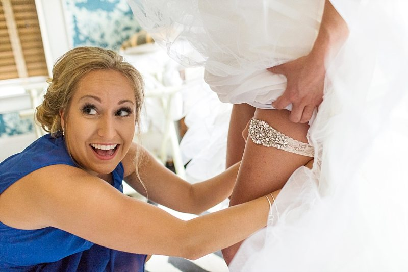 A bride's sister laughs as she slides the garter on to the bride's leg.