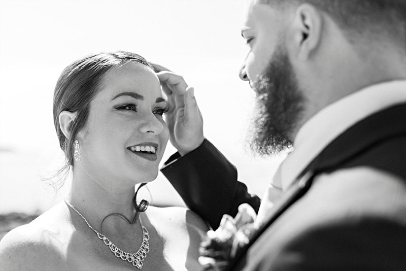 A bride smiles at the groom as he sweeps hair out of her eyes.