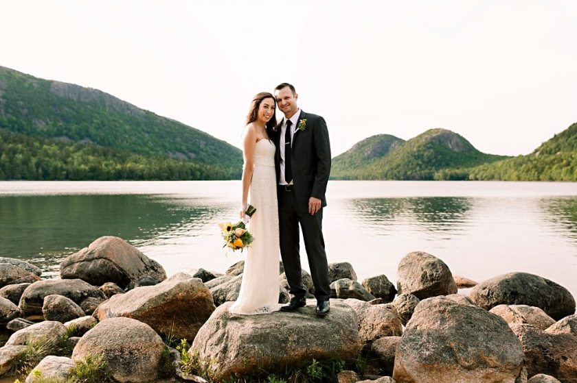 Bride and groom pose for a wedding portrait at Jordan Pond in Acadia National Park.