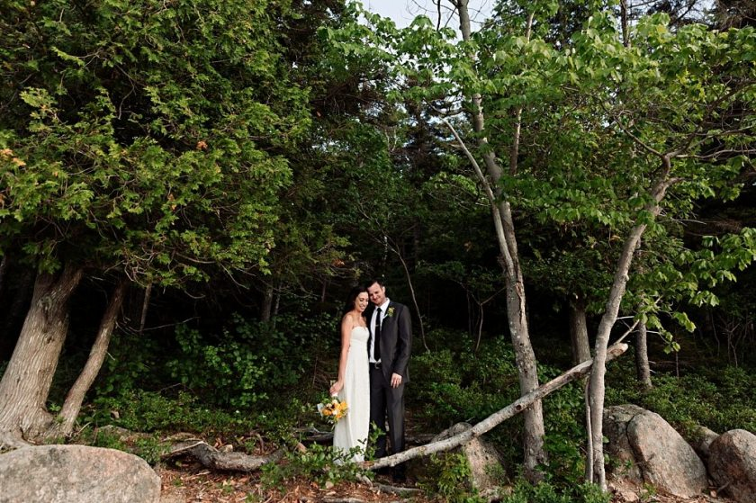 Bride and groom stand in the woods at Jordan Pond.