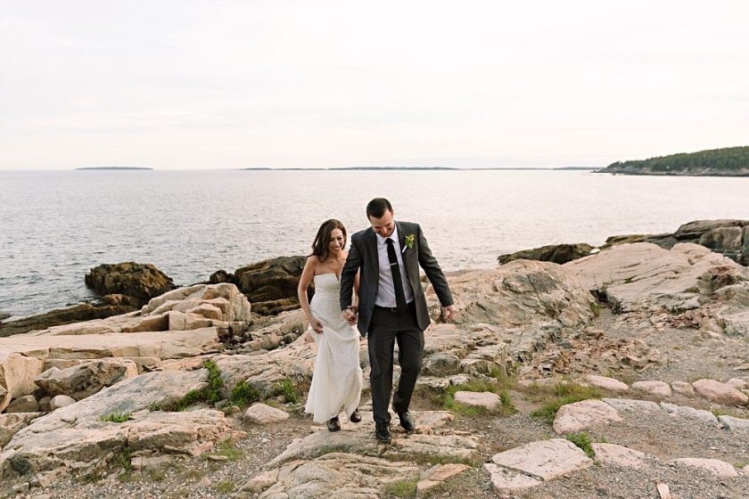 Bride and groom strolling together in Acadia National Park.