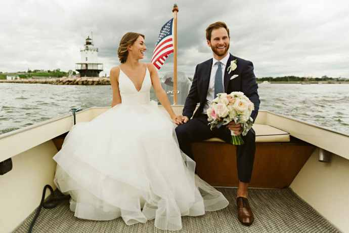 Bride and groom on boat in front of lighthouse